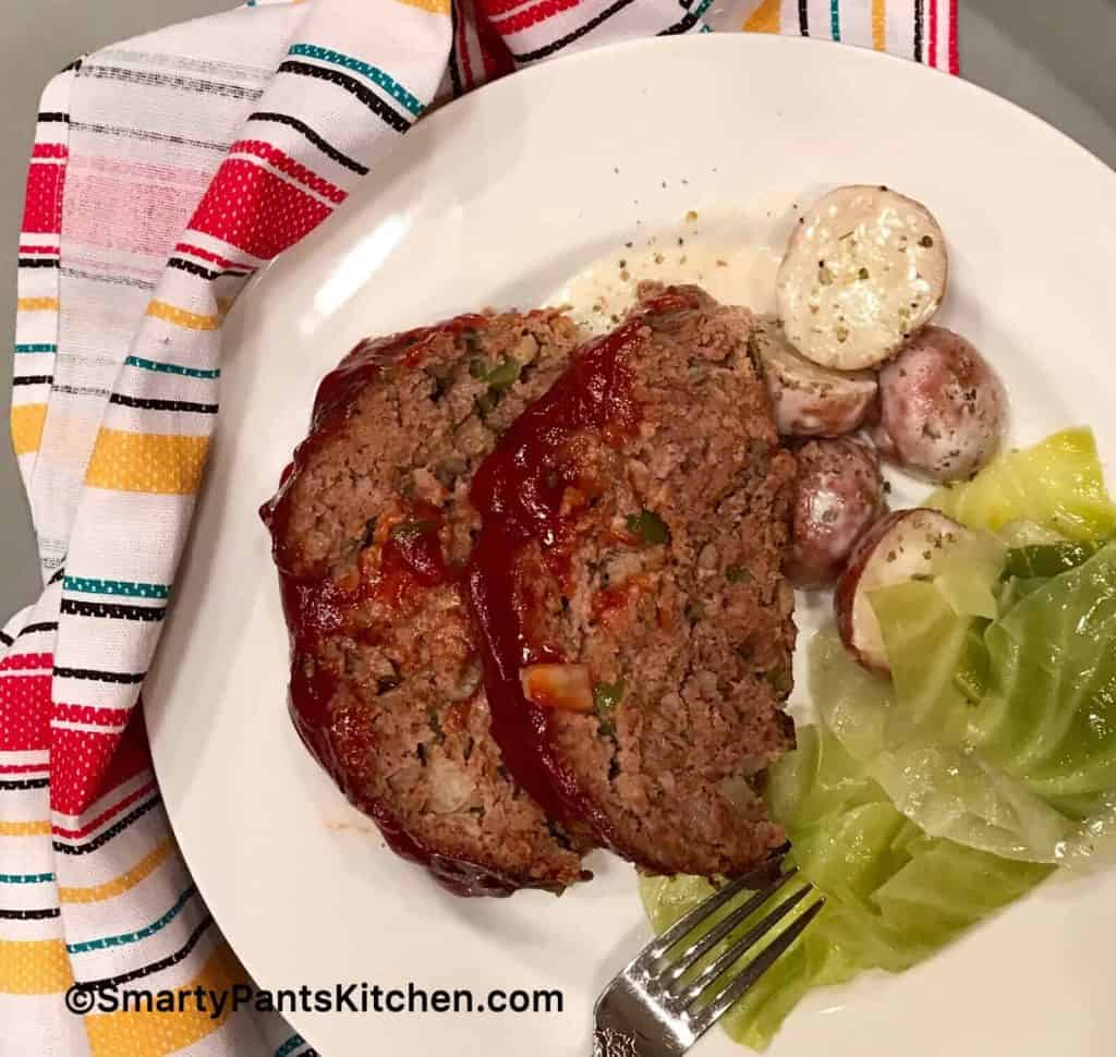 Meatloaf, cabbage and potatoes on white plate