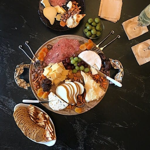 Round wooden serving tray with cheese, grapes, salami and serving utensils