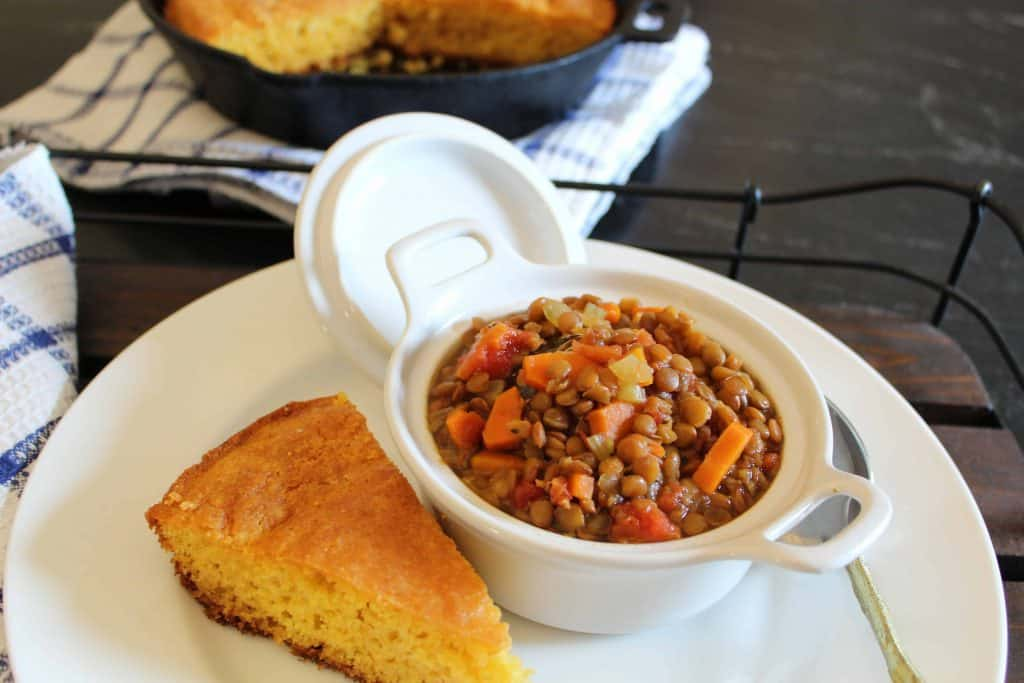 Lentil Soup in white bowl with a slice of cornbread