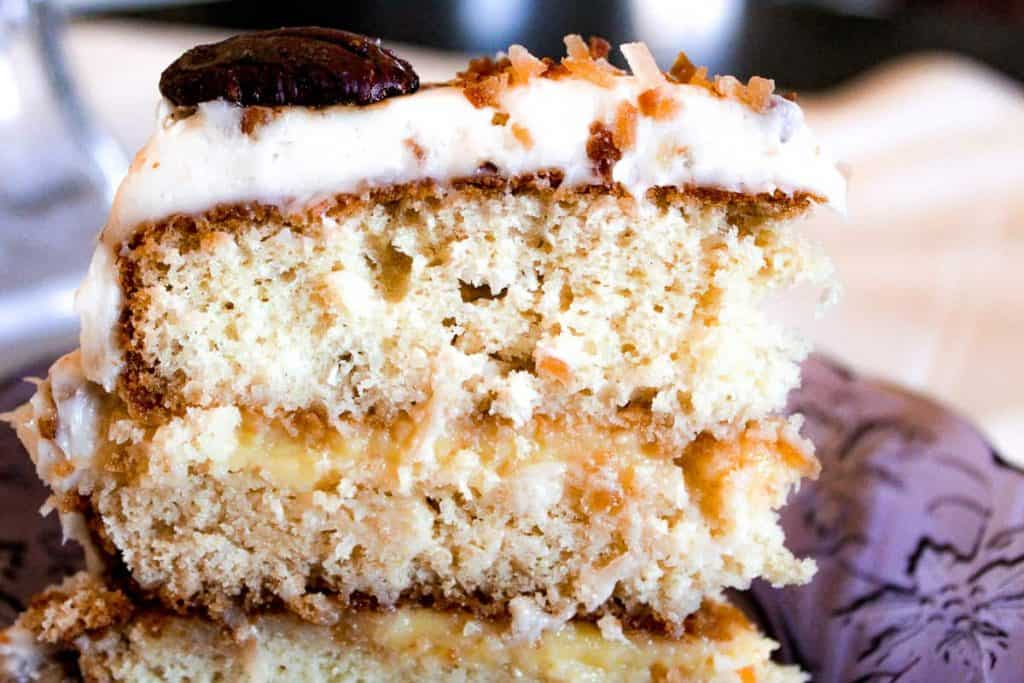 Side view of Orange Italian Cream Cake layered with orange curd and topped with toasted coconut