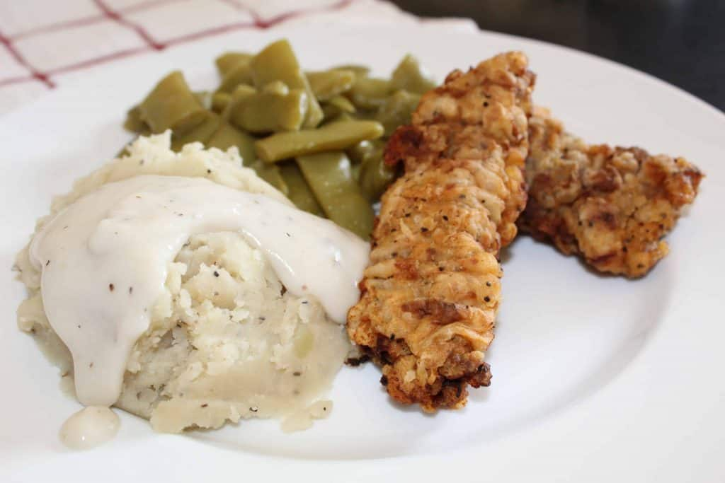 Chicken Fried Steak fingers, mashed potatoes with gravy on plate