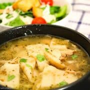 Chicken and dumplings in black bowl with side salad