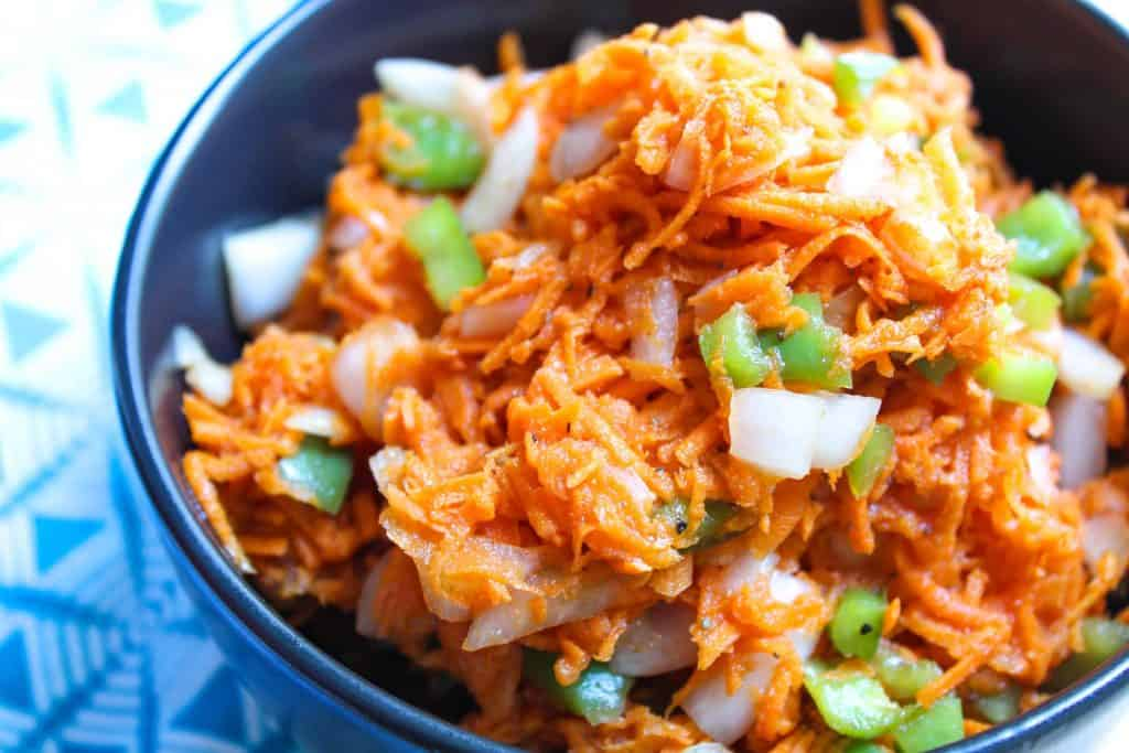Shredded carrots with onion and green bell peppers in a bowl
