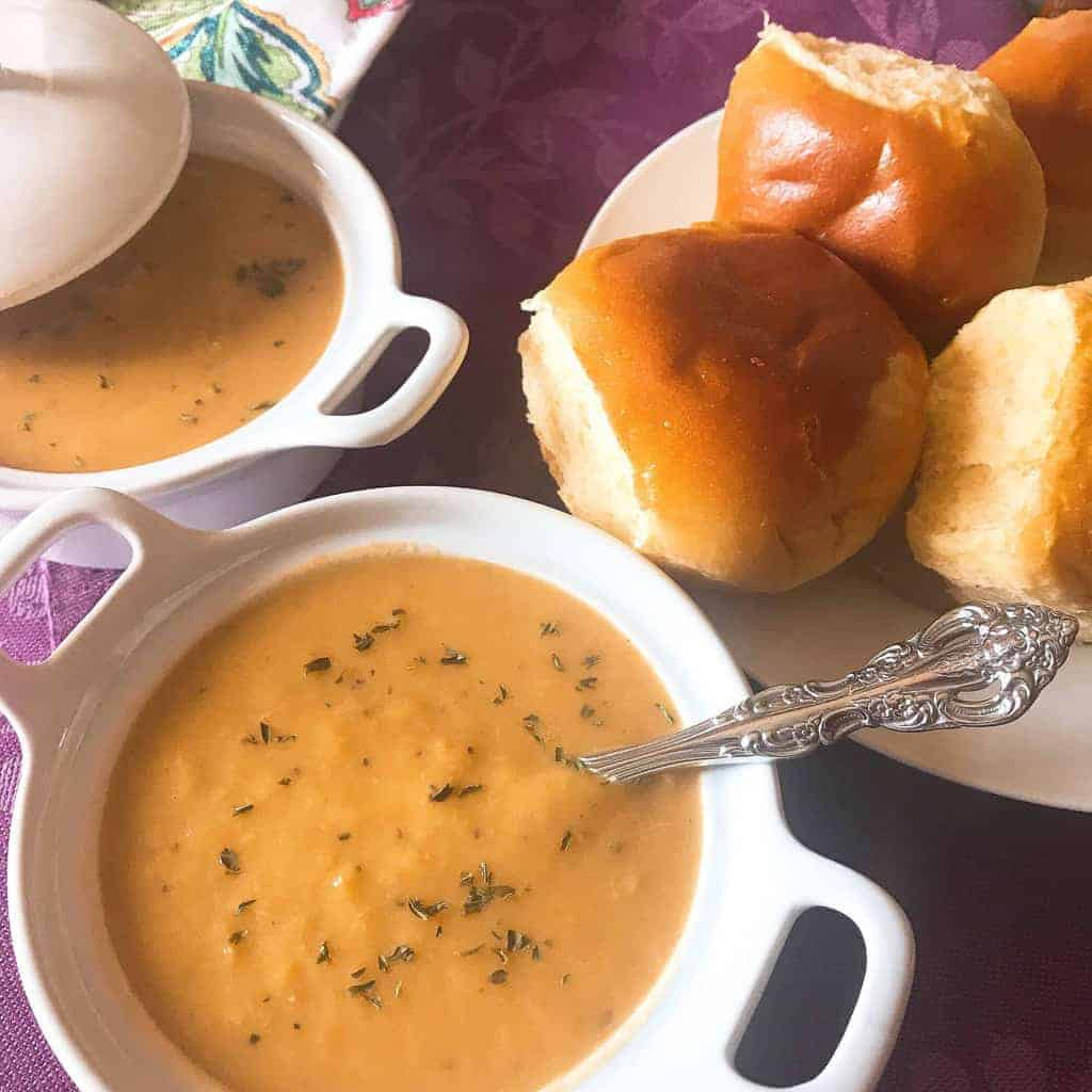 Two white bowls of leek soup with a plate of rolls