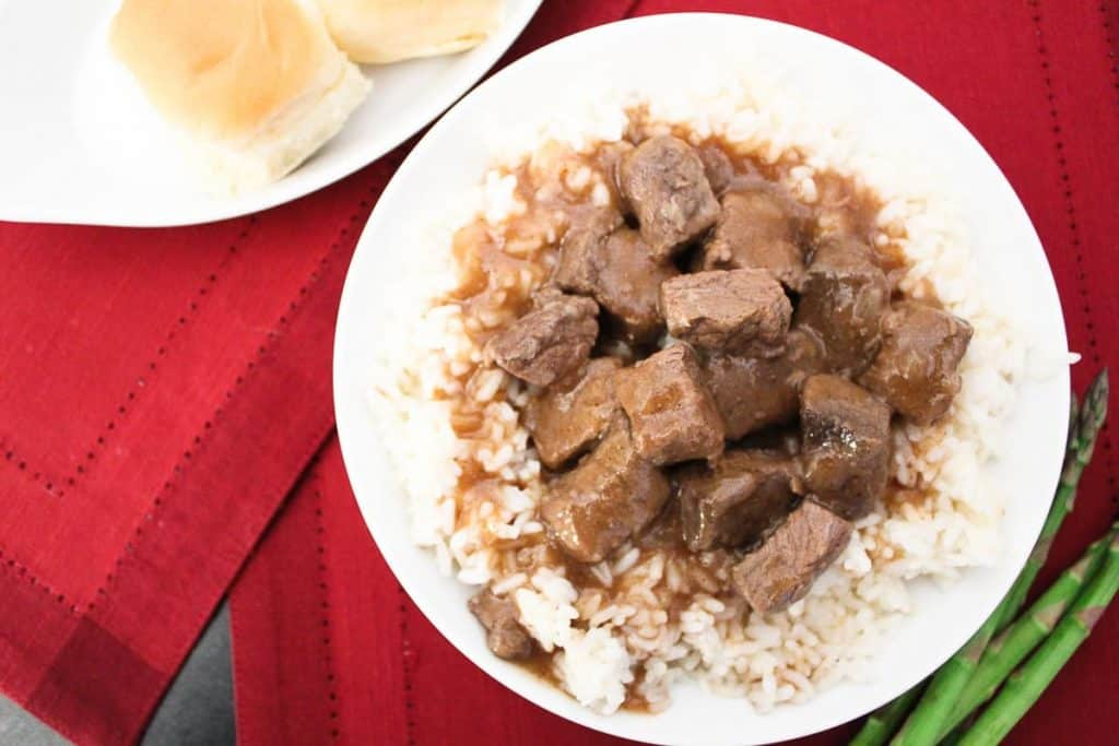 Beef tips and gravy with white rice, a side of rolls and asparatus on the side
