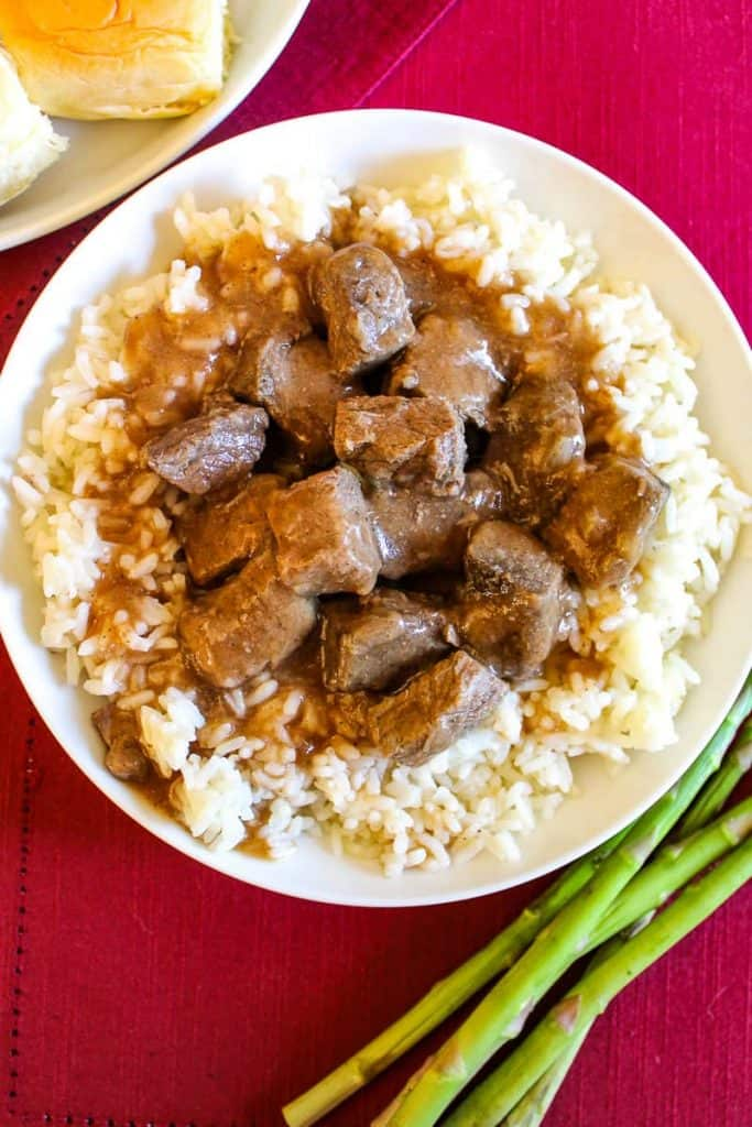 Tender bites of beef sirloin nestled in a brown gravy and served over white rice in a white bowl with a roll and asparagus on either side of the image