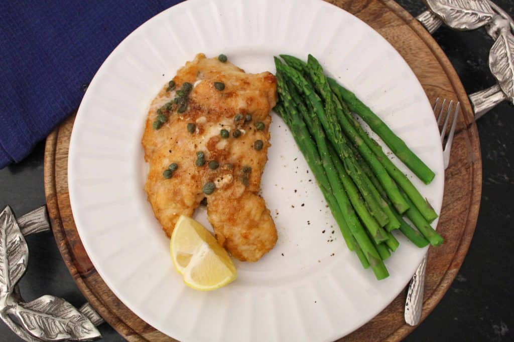 Chicken Piccata topped with capers and a side of asparagus on white plate