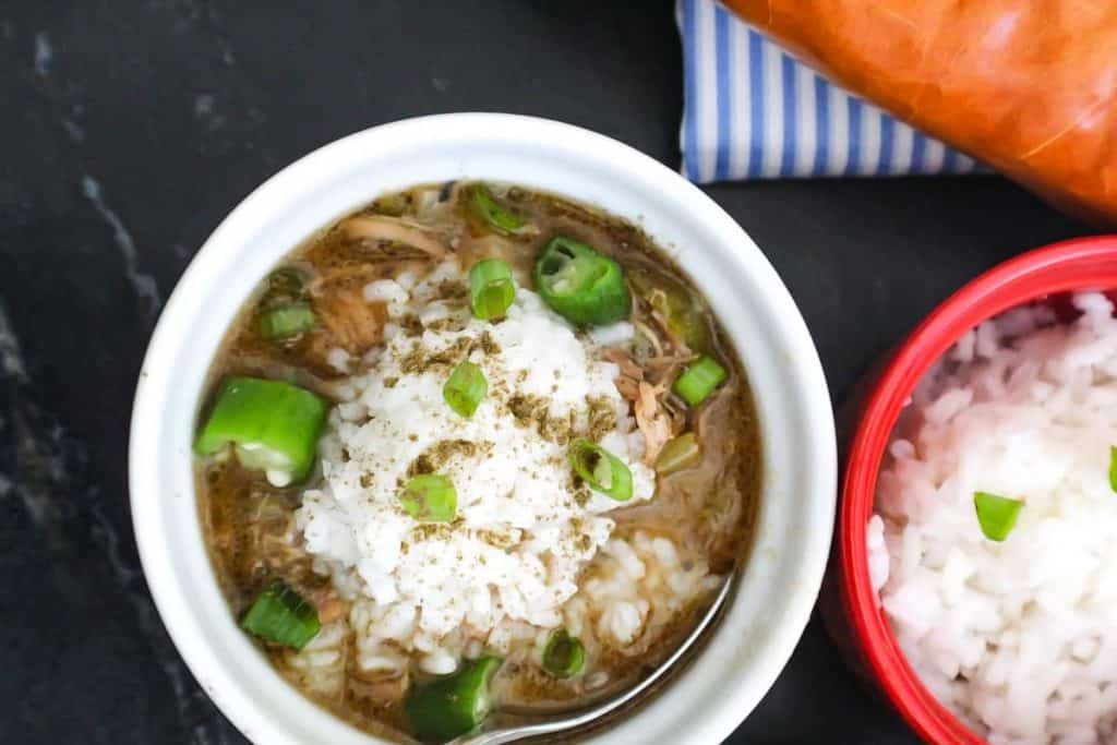 Bowl of New Orleans Cajun Chicken Gumbo with rice, garnished with file powder and green onions