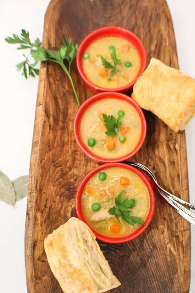 Three red bowls of chicken pot pie soup on a brown tray with puff pastry on the side