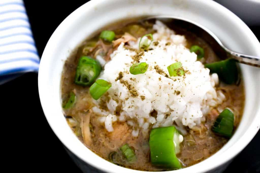 New Orleans Cajun Chicken Gumbo served with white rice, garnished with file powder and green onions
