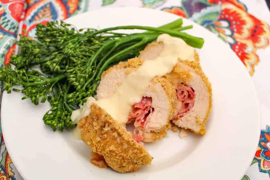 Sliced chicken cordon bleu with dijon sauce and a side of broccolini on a plate