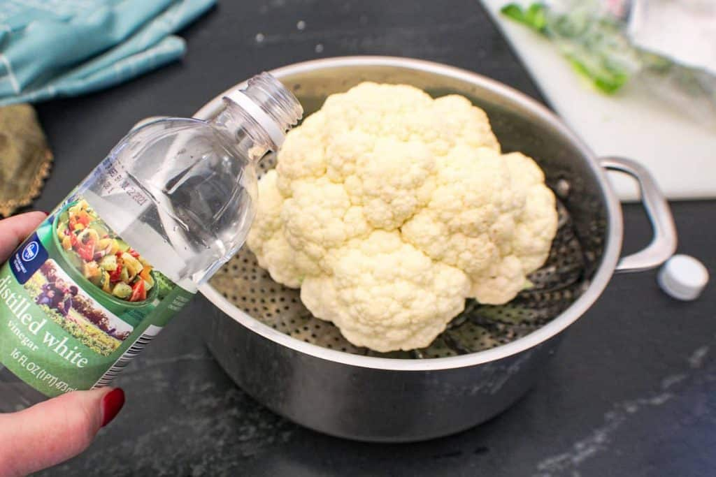 Pot with a head of cauliflower and someone adding vinegar to the water
