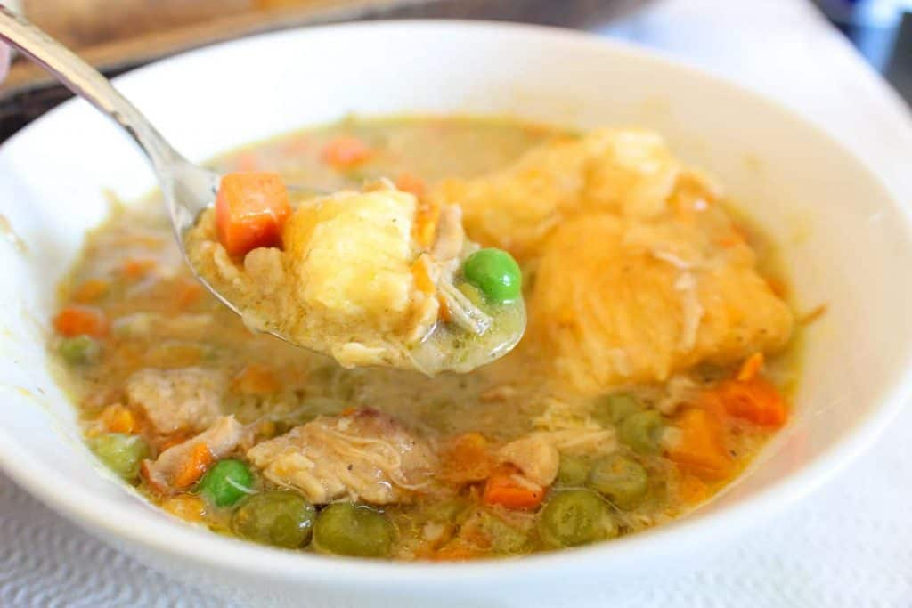 spoonful of chicken pot pie over a bowl of soup with submerged pastry