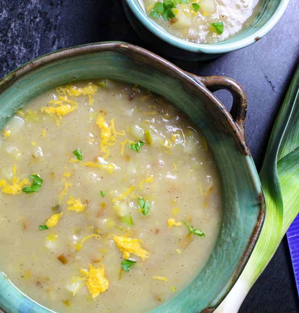 Green bowl of creamy vegan potato leek soup