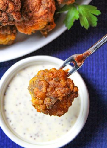 Holiday Sausage Ball on fork resting over honey mustard dip