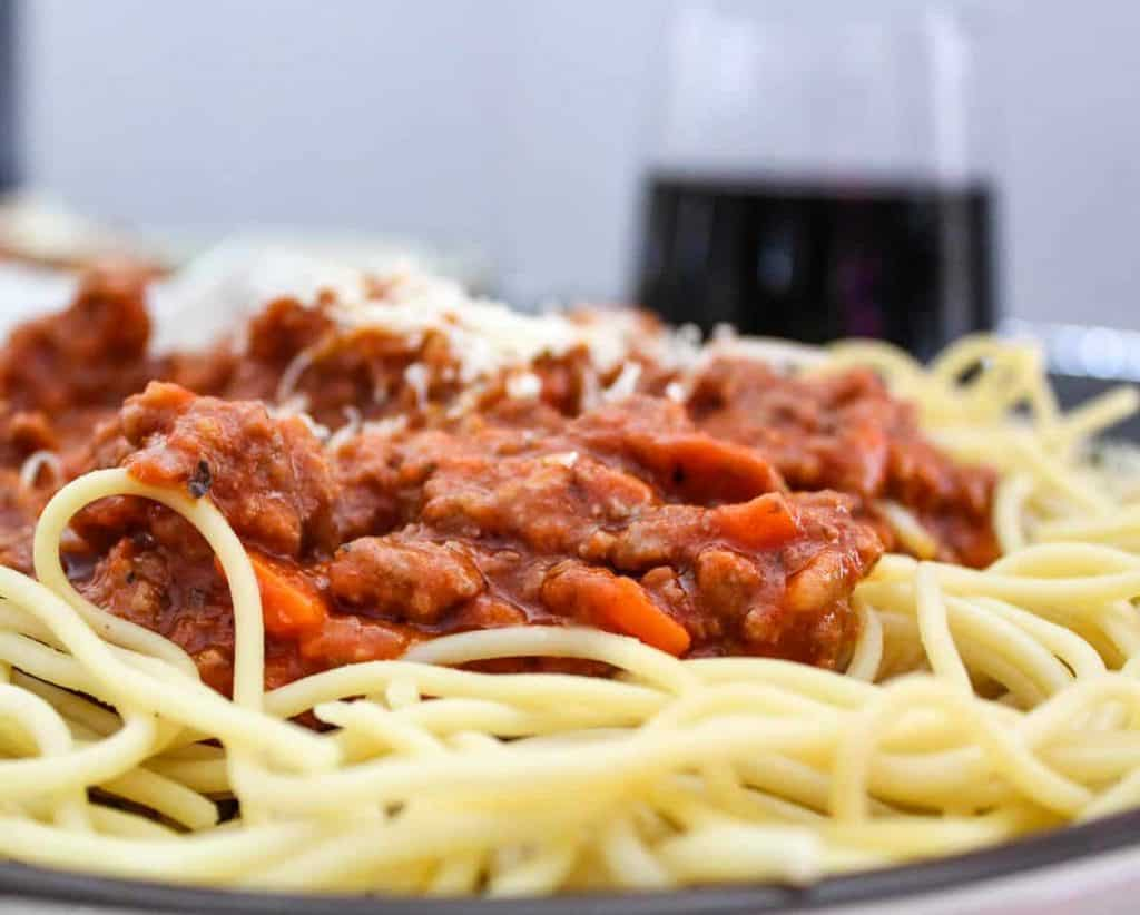 Close up view of meaty bolognese sauce over spaghetti