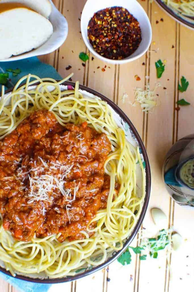 Bowl of spaghetti noodles topped with rich, thick meaty bolognese sauce and a side of bread