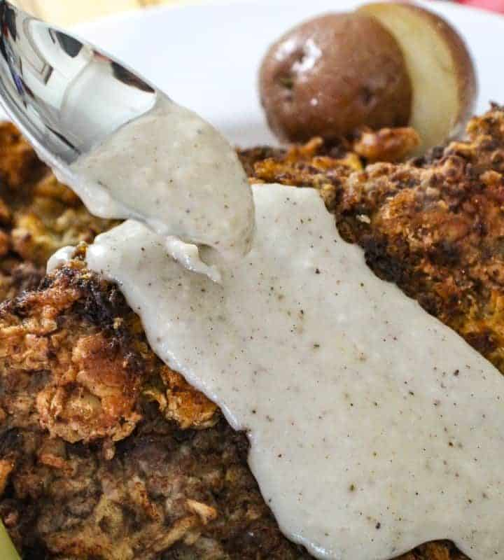 Cream gravy being spooned over chicken fried steak
