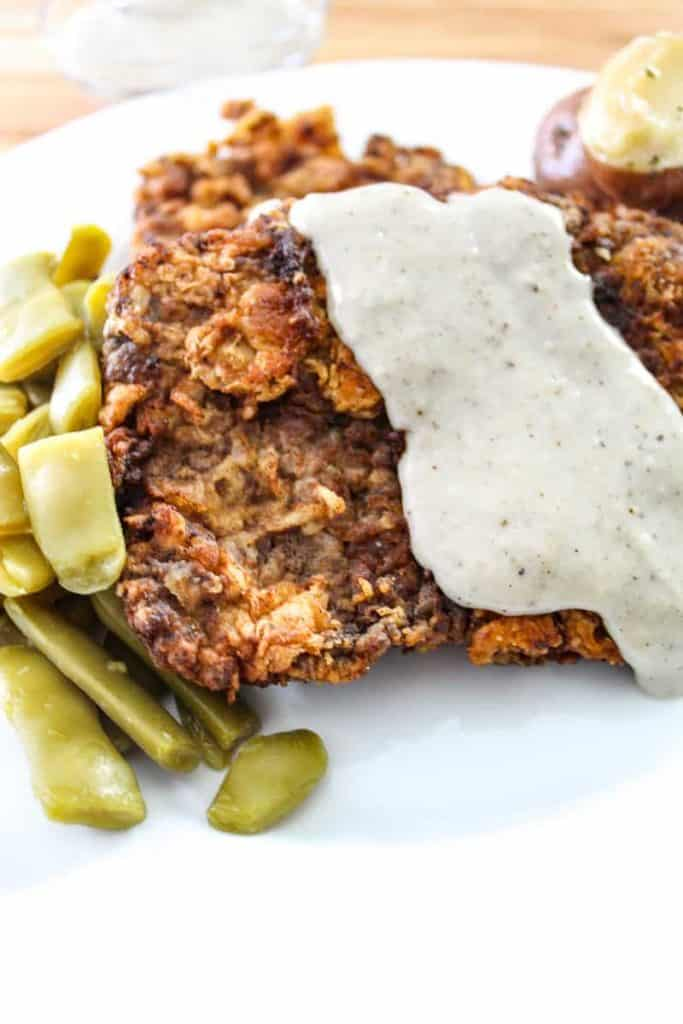Chicken Fried Steak with Cream Gravy and green beans on plate