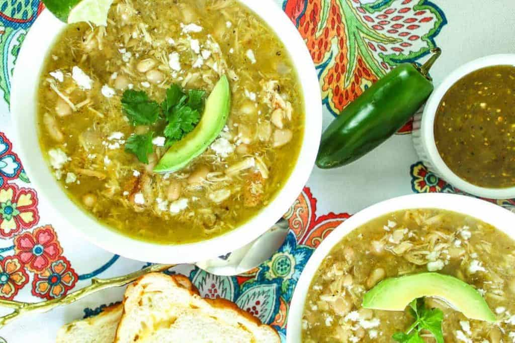 Two bowls of green chile soup garnished with cilantro, cotija cheese and avocado