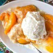 Peach Cobbler topped with vanilla ice cream in white oval dish