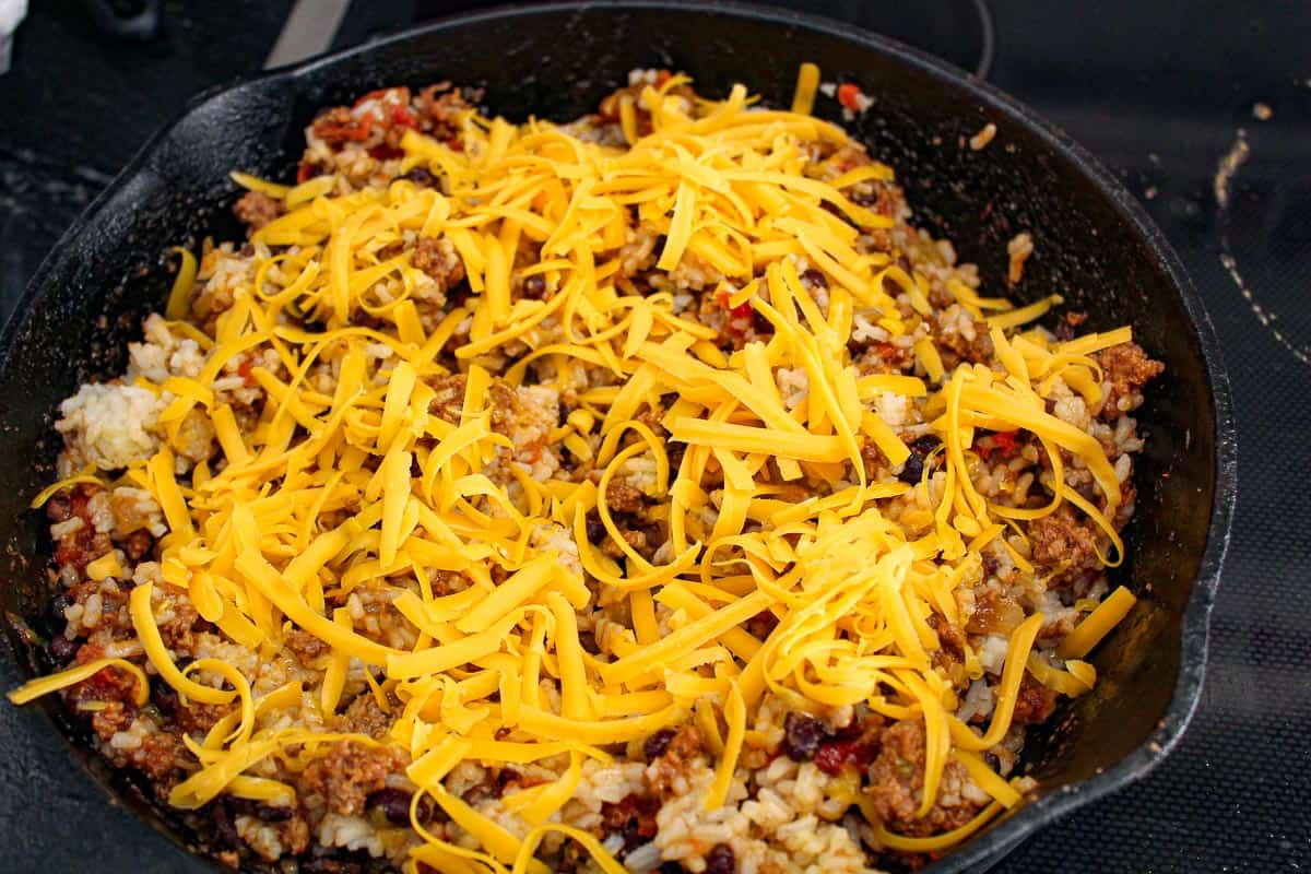Shredded cheddar cheese over beef and rice in cast iron skillet