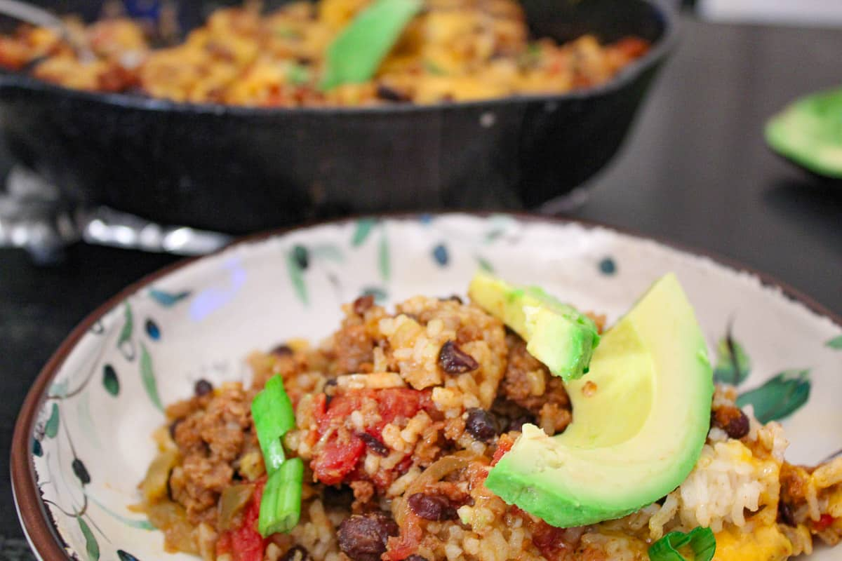 Mexican Skillet Supper in decorative bowl garnished with sliced avocado