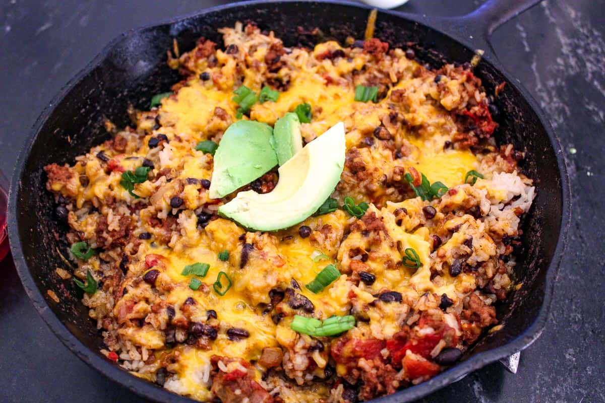 Mexican skillet supper in cast iron skillet garnished with green onion and avocado