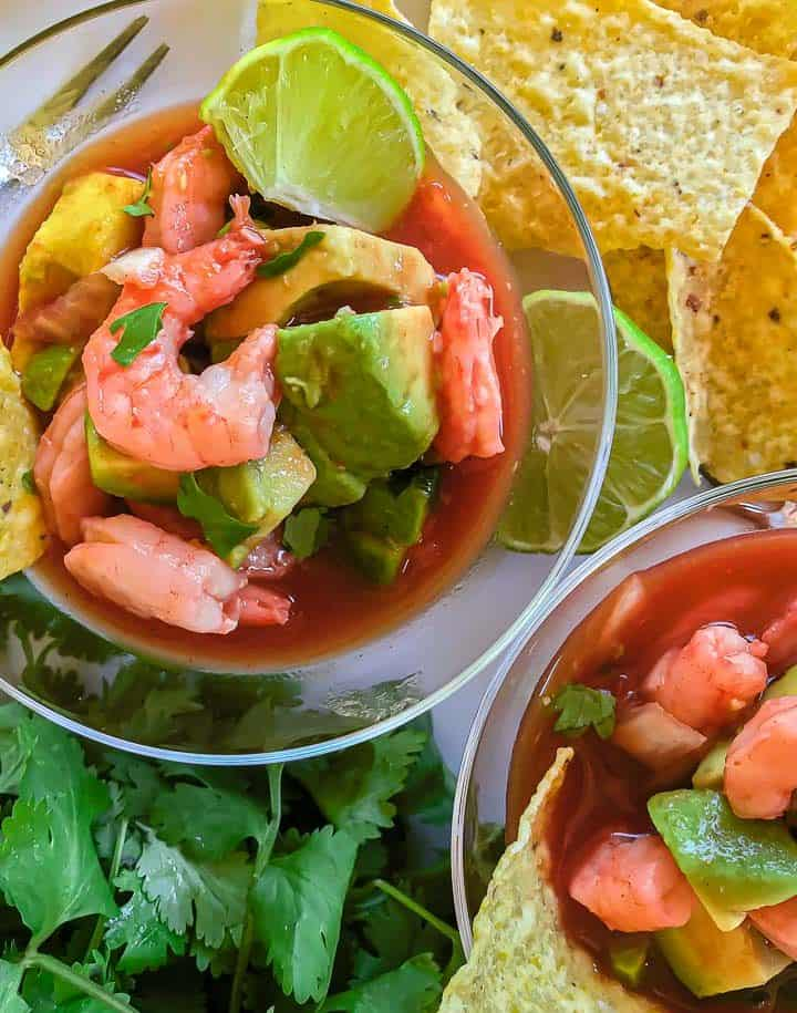 Shrimp and avocado in tomato broth in clear bowl with lime and tortilla chip garnish