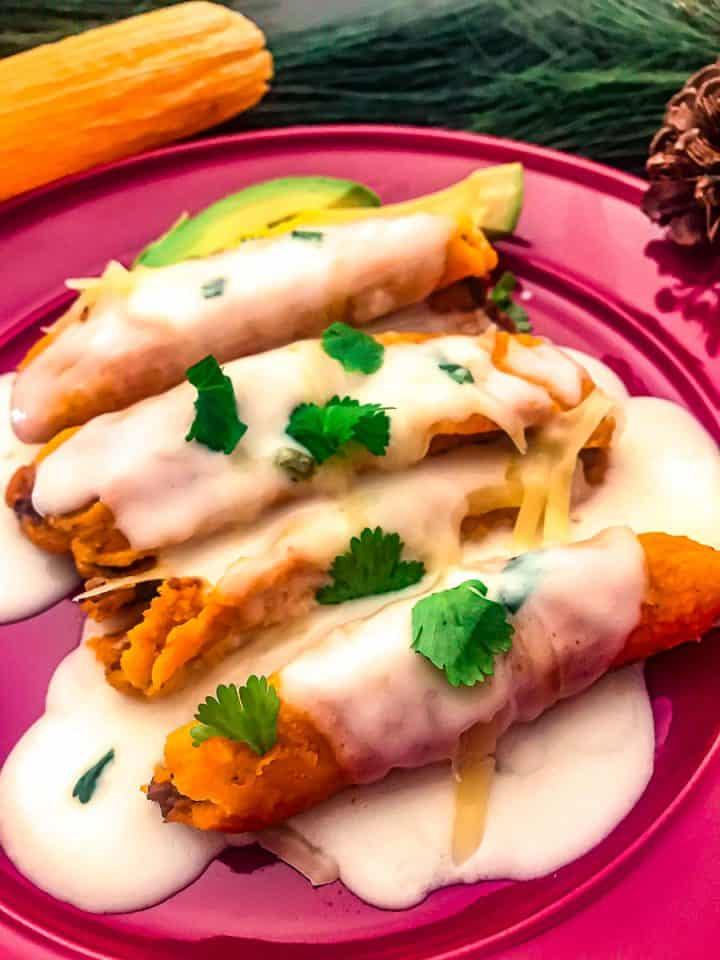 Tamales topped with Tex-Mex Sour Cream sauce and garnished with cilantro on a purple plate