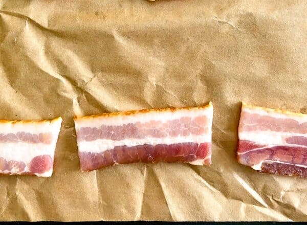 A strip of bacon cut into thirds on brown butcher paper