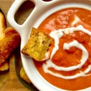 Smoked tomato bisque on brown serving tray with crouton and cream