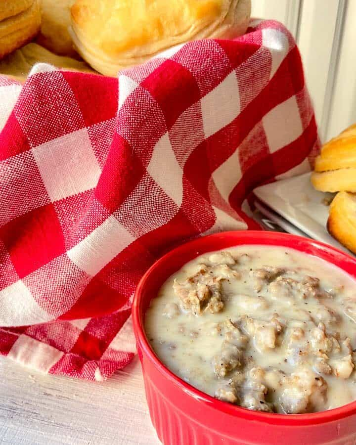 Sausage cream gravy in red bowl with bowl of biscuits in red checkered basket in background