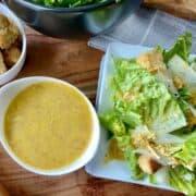 Caesar dressing in small bowl next to Caesar salad